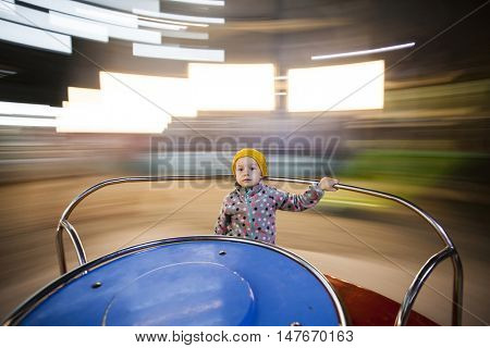 Happy girl having fun on the roundabout