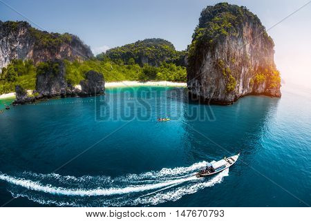 Aerial view of clear sea with traditional longtail thai boats and the mountain on the background