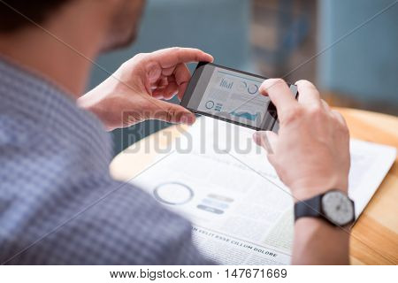 Unbreakable news. Screen mockup of smart phone that a man using and making photo of newspaper while sitting at the table