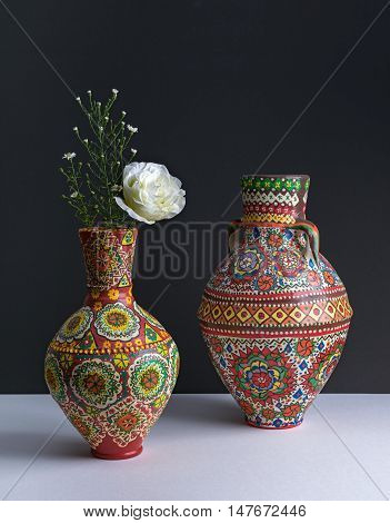 Still life composition of two colorful pottery vases white flower and small flowers on background of white table and dark wall