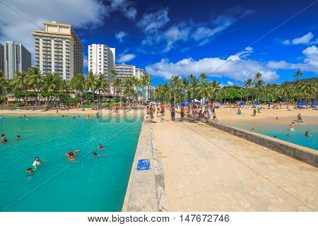 Waikiki Oahu Hawaii - August 27 2016: skyline of Waikiki from the Waikiki Walls or Waikiki Pier between Kuhio Ponds and Queen's Beach two sections of the popular Waikiki Beach in Honolulu Hawaii.
