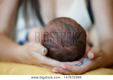 Little newborn baby, brunette with soft sparse hairs comfortably sleeps on a soft orange blanket, the mother tenderly put her head under his hands the kid, on fingers of mother-blue and pink nail polish