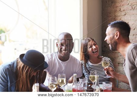 Joyful group of young adults drunk from wine laughing while seated at dinner table with bright window and brick wall in background