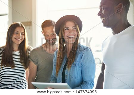 Diverse group of four happy attractive adults dressed as students looking at tablet with bright office or school window behind them