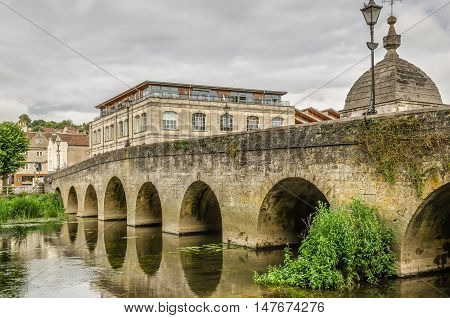 Old stone bridge over River Avon in Bradford on Avon, Wiltshire, England on overcast day.