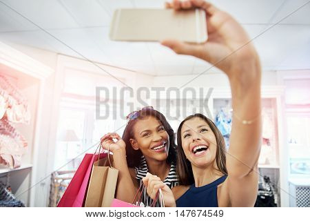 Laughing vivacious young women posing for a selfie together in a fashion store as they hold up their purchases in colorful bags