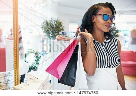 Chic elegant young African woman out shopping standing in a clothing store with her purchases in bags over her shoulder wearing trendy sunglasses