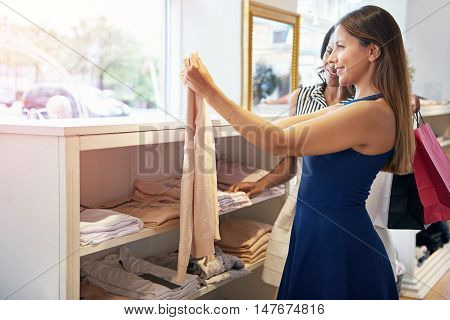 Two young women shopping in a clothing store holding up a top for appraisal with happy smiles three-quarter side view