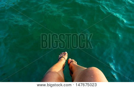 relax motion woman leg sitting over the sea on the briged at seaside