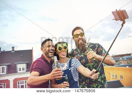 Trio of happy friends with open beer bottles in hand and selfie stick taking a picture of themselves on top of roof in city