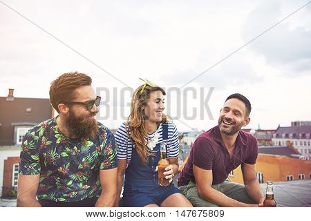 Cheerful group of young adults drinking beer from bottles on roof outdoors during summer with copy space in sky