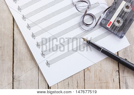 music paper, fountain pen, tape cassette on wooden table