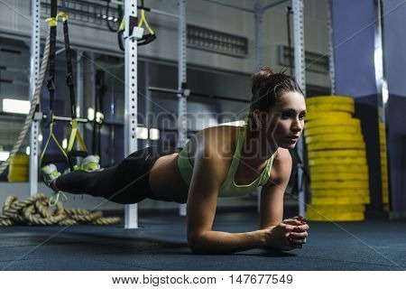 Concept: power strength healthy lifestyle sport. Powerful attractive muscular woman fitness trainer stand in plank during workout at the gym