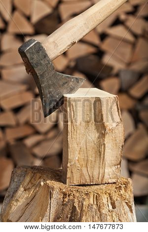 Chopping firewood detail with wooden block and axe