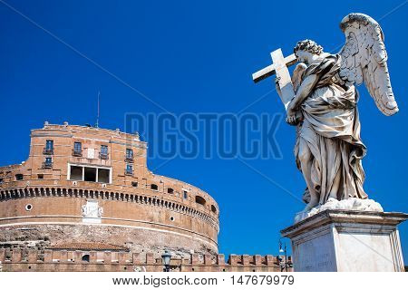 ROME, ITALY - September  13, 2016: Statue of Angel with the cross and Castel Sant'Angelo on the background. Ponte Sant'Angelo, Angelo Bridge.Aelius. Rome. Italy.