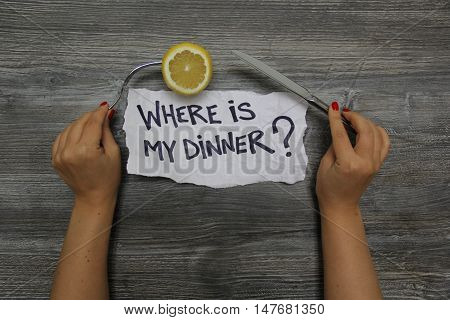 Where is my dinner? Fork with lemon in the left hand and knife in the right hand on the gray wooden textural background