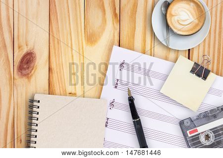 music paper, fountain pen, tape cassette and coffee latte on vintage wooden table flat ray