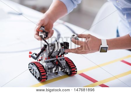 New life. Male hands carefully put details of a robot together