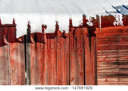 Snow sliding slowly down on a tin roof of a red barn.