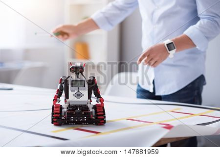 Happy moment. Male inventor finishing his work on a cute robot sited on the table