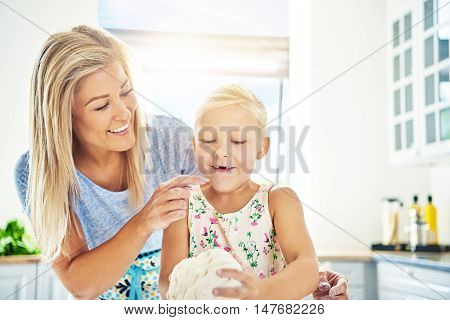 Cute happy little girl missing her front teeth learning to bake with her mother in the kitchen as she helps with kneading the dough