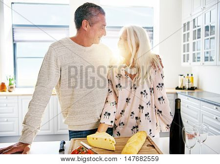 Man and woman at kitchen counter standing together with bright sunlight shining between them