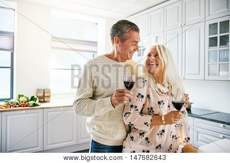 Vivacious healthy elderly couple drinking wine together in the kitchen in a loving embrace as they enjoy their retirement high key with copy space