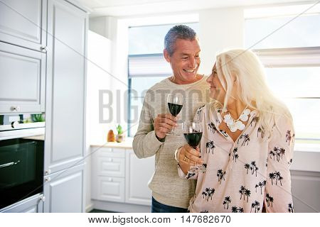 Happy retired couple enjoying a glass of wine together in a fresh white kitchen as an aperitif to a meal