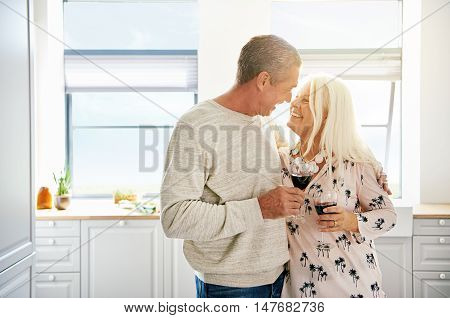 Elderly retired couple sharing a tender moment with the husband embracing his wife and looking deeply into her eyes as they enjoy a glass of red wine in the kitchen