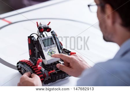 New try. Man turning a small robot on while making an experiment