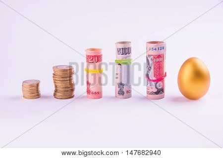 A gold egg placed vertically in 1 line with rolls of indian money or indian paper currency tied with rubber band, isolated over white background