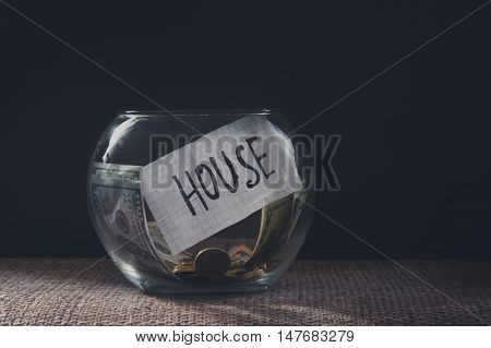 Savings money jar with coins for a house