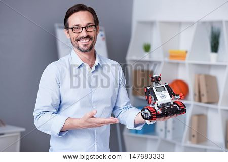 Buy this. White male with a beard showing a new electronic device.