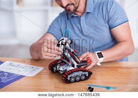 Exciting job. Male hands putting pieces of robot together