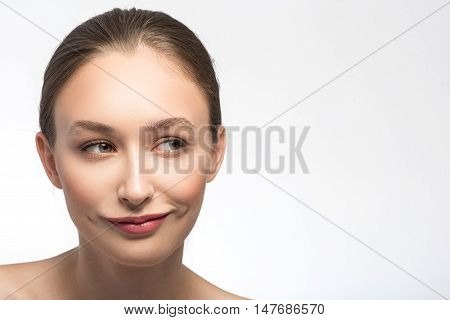 Sly young woman is standing and smiling. She is looking aside with curiosity. Isolated and copy space in right side