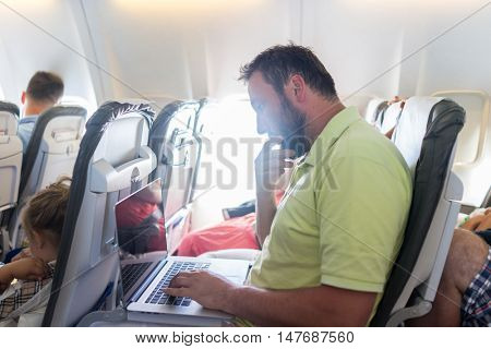 Businessman with laptop in airplane