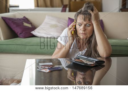 middle aged woman on a phone worried about her finances