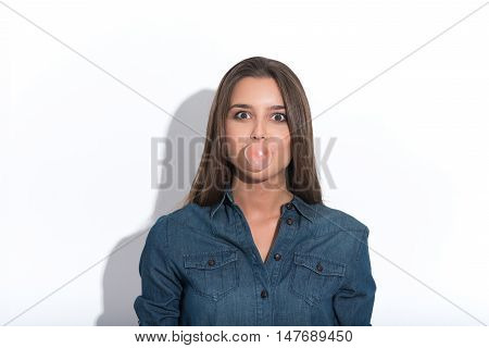 Playful girl is blowing gum with joy. She is standing and staring at camera. Isolated