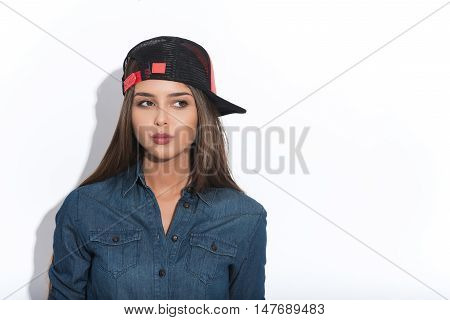 Pretty young woman is standing and looking aside with suspicion. She is wearing cool cap. Isolated and copy space in right side