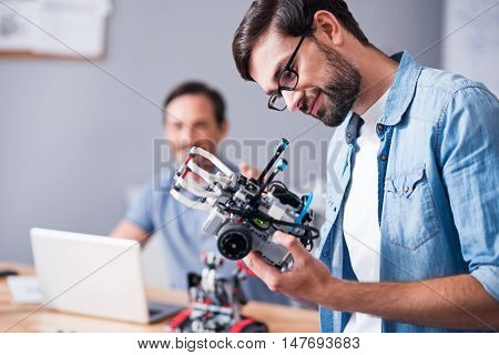 Rely on technologies. Positive professional man holding robot and testing it while his colleague using laptop in the background