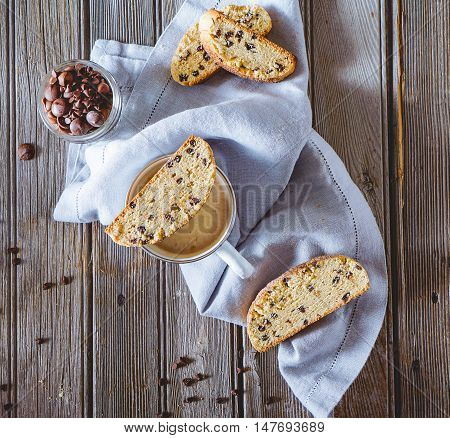 Coffee with biscotti or cantuccini with chocolate chips on wooden vintage table, traditional Italian biscuit or cookies.