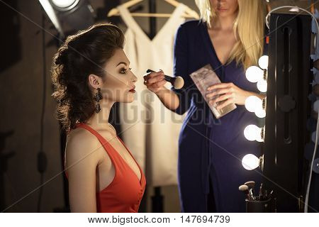 Confident young model is preparing for podium in dressing room. She is sitting in front of mirror. Female beautician is standing near her and holding powder brush