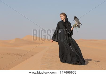 Woman in traditional emirati dress, called abaya, with falcon on her arm in a desert