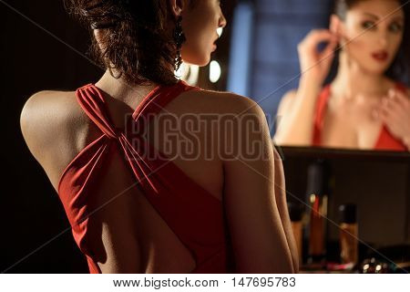Glamorous young woman is preening in front of mirror. She is sitting and wearing earring with concentration. Focus on her back