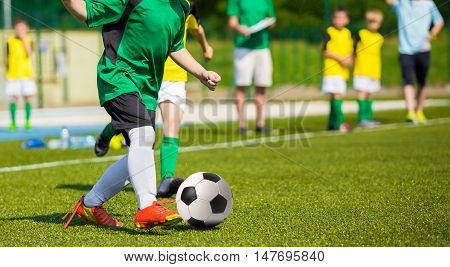 Training and football match between youth soccer teams. Young boys playing soccer game. Soccer competition between yellow and green team.