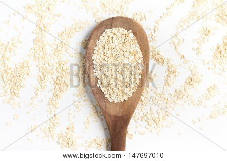 Quinoa Flakes into a spoon isolated in white background.