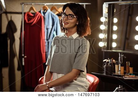 Happy young woman is sitting on chair in dressing room. She is looking at camera and smiling. Clothing and mirror with cosmetics on background