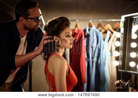 Professional stylist is touching female hair with creativity. Man is looking at mirror with seriousness. Young model is sitting backstage