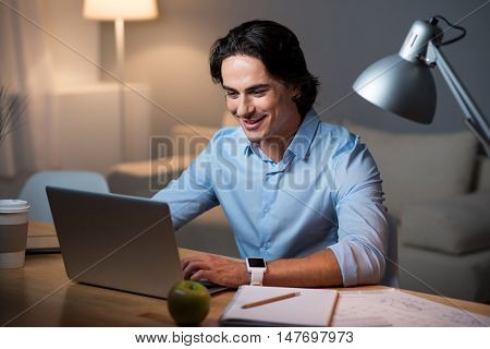 Interesting information. Enthusiastic young handsome man smiling and using laptop while sitting at the table.