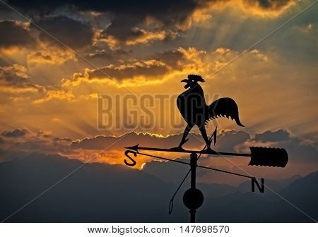 Silhouette of weather vane on background of colorful cloudscape